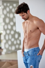 nude shirtles handsome young man in jeans posing at modern home indoors